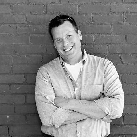 A black and white photo of an EPB middle-aged male customer is leaning against a brick wall, smiling at the camera.
