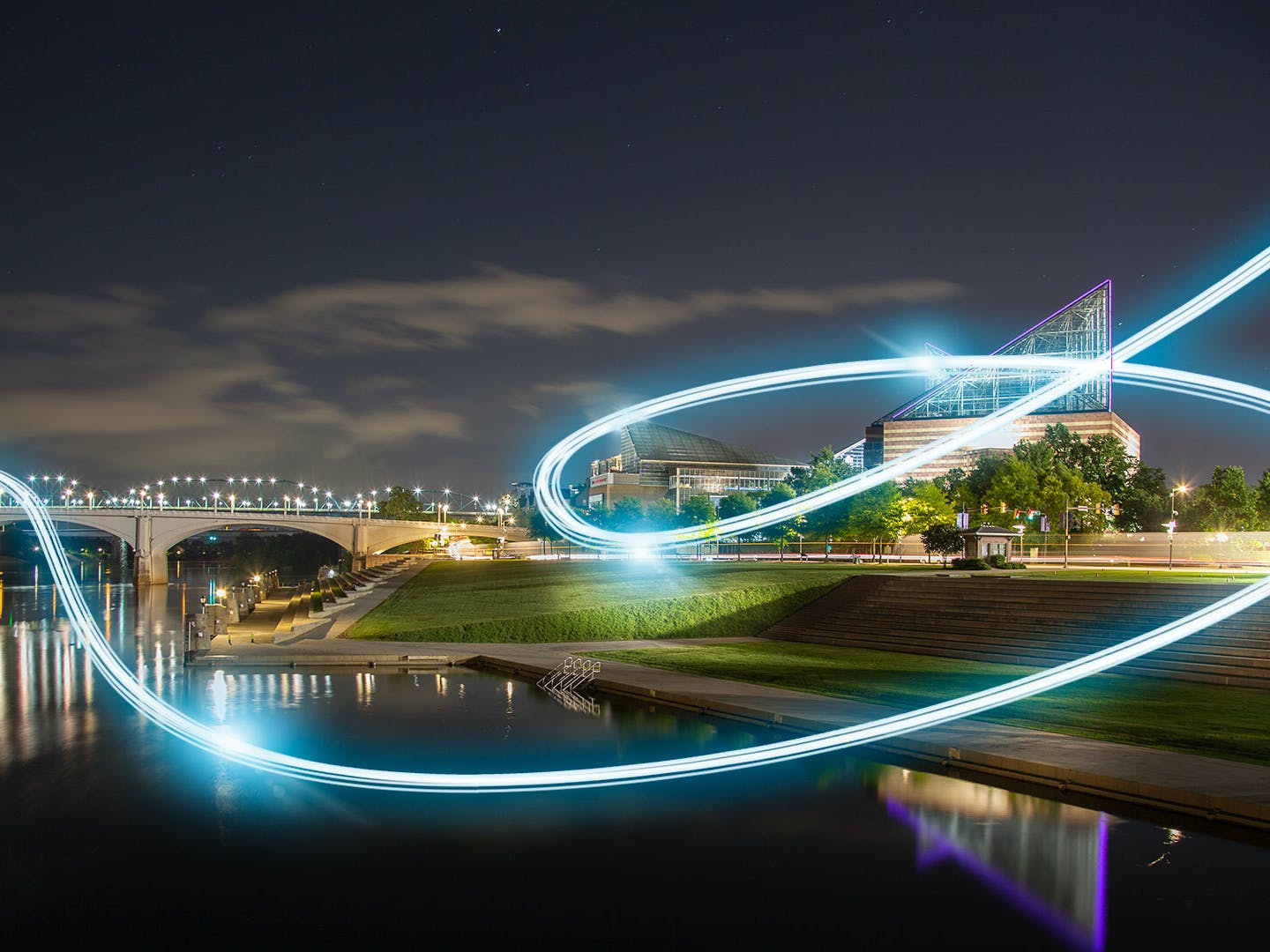 View of the Tennessee Aquarium at night from across the river with fiber light streaks in sky