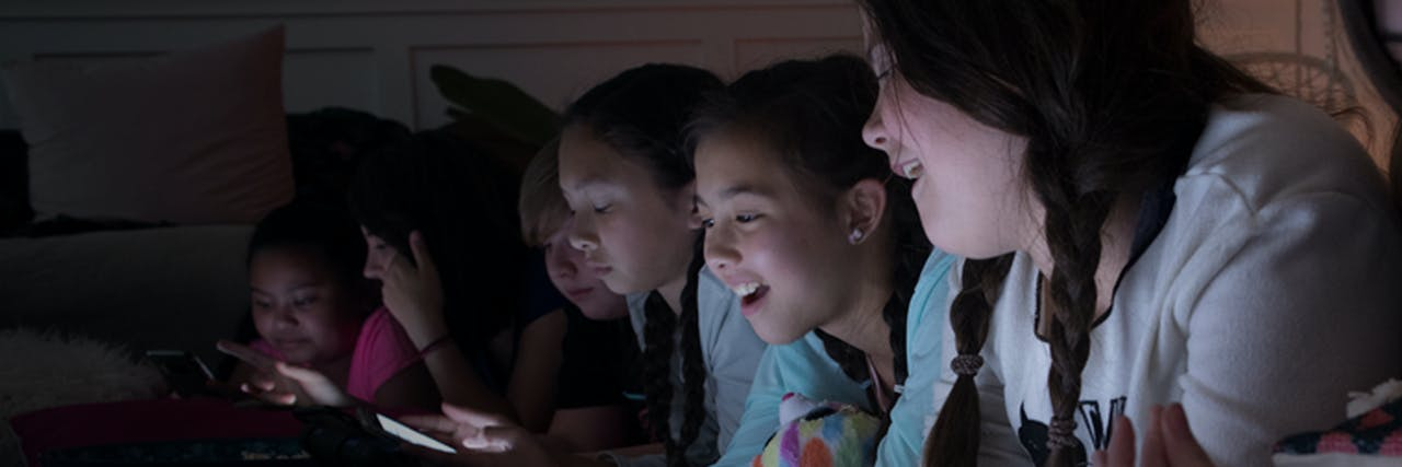 A group of pre-teens girls areat a slumber party. They are all on their devices, laughing and sharing images.
