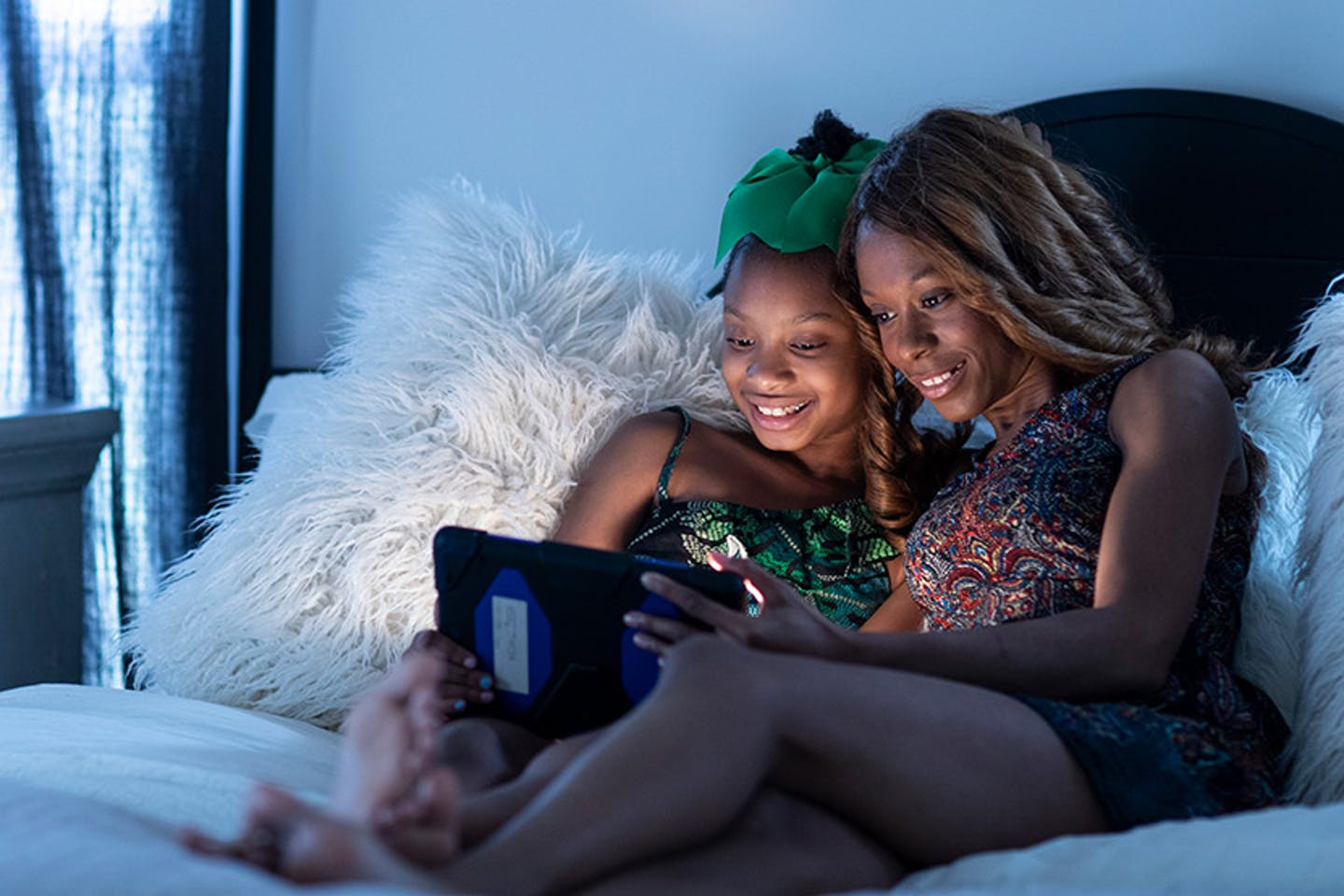 Mom and daughter streaming TV in bed.