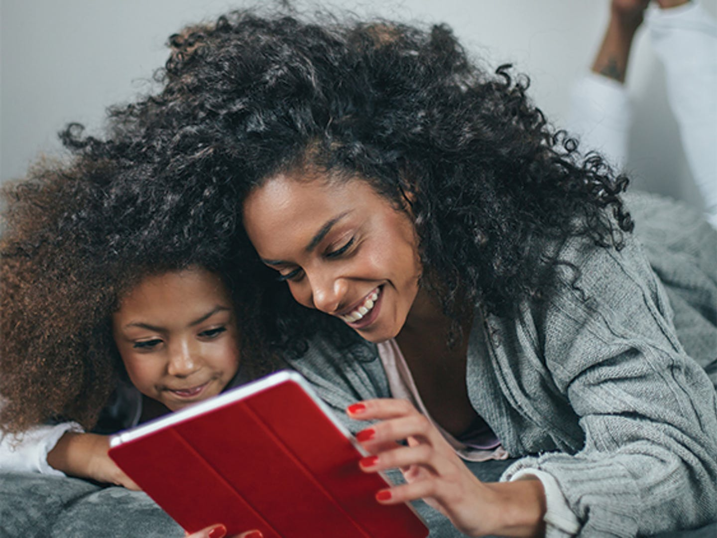 African-American mother and daughter are laying on a bed, laughing and watching an iPad.
