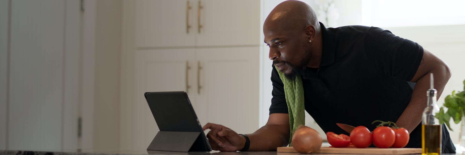 African-American man is cooking and using the internet on his iPad.