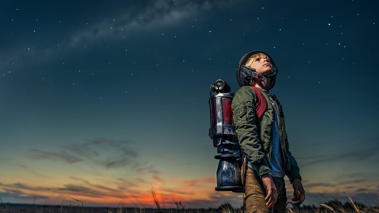 Young boy looking up at a futuristic-looking night sky.