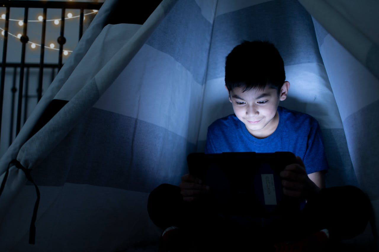 Young boy looking at an iPad inside a tent in his bedroom.